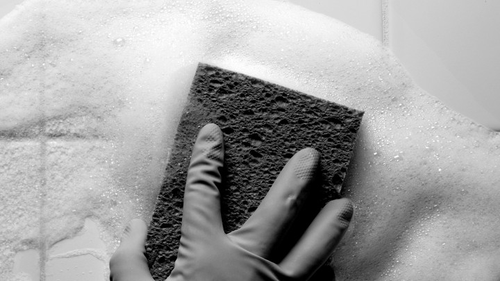 A gloved hand using a sponge to clean a tiled wall