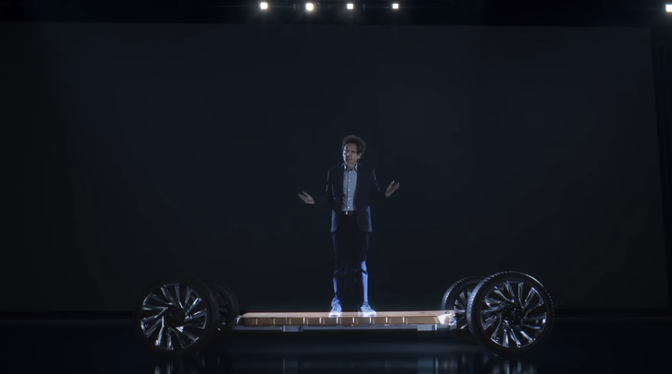 The writer Malcolm Gladwell stands on an electric-car chassis and shrugs