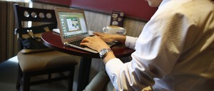 A man works on a laptop in a cafe.