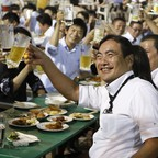 Tokyo businessmen and women raise beer mugs in a toast at an after-work party.