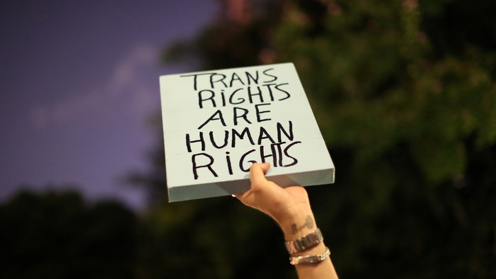 "A hand holding a sign that reads ""Trans Rights Are Human Rights"""