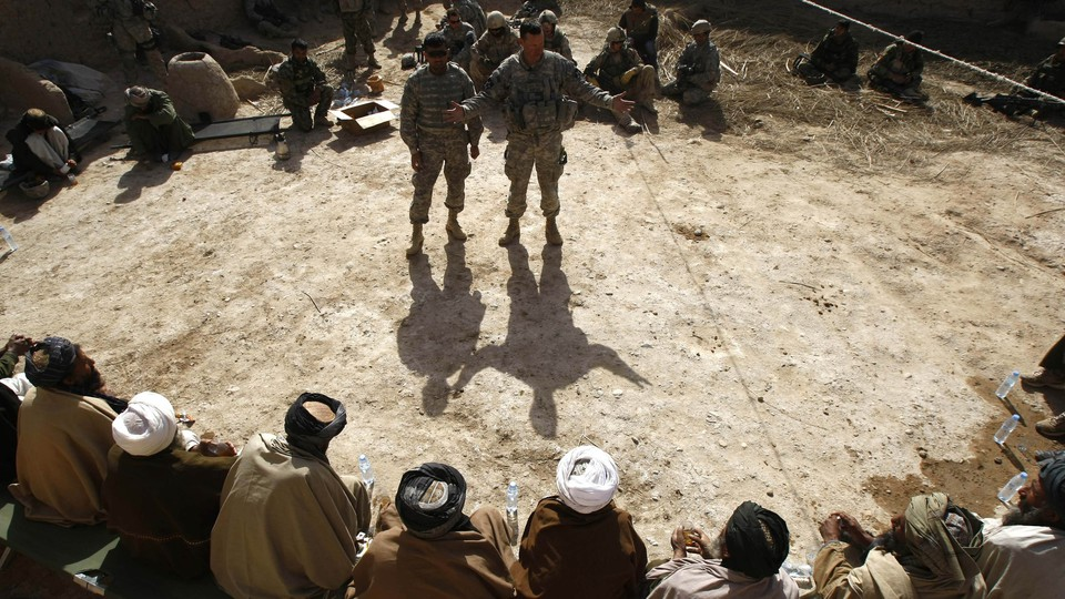 Interpreters being addressed by two soldiers in Afghanistan