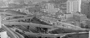 an aerial view of Los Angeles shows the complex of freeways, new construction, familiar landmarks, and smog in 1962.