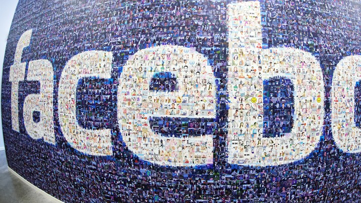 A wide-angle photograph of a wall plastered with the Facebook logo made of smaller photos