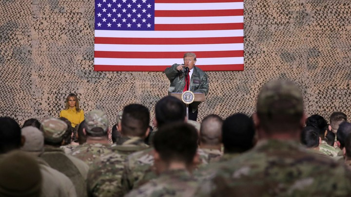 Donald Trump speaks to troops at al Asad Air Base with an American flag behind him and Melania Trump next to him.