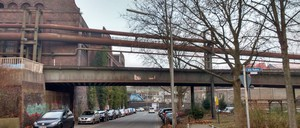 A city overpass with parked cars and sparse trees
