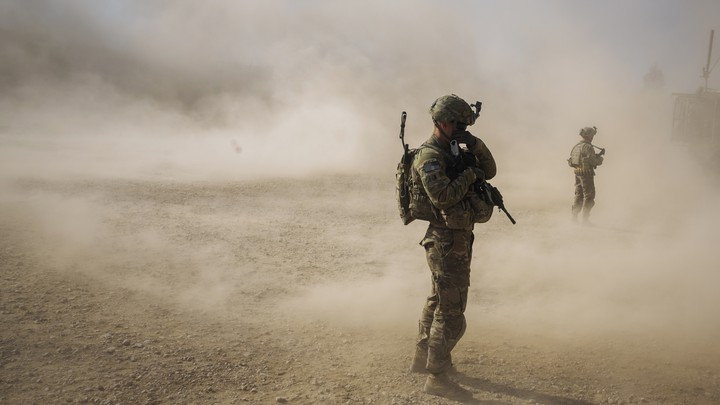 U.S. soldiers cover their faces from the dust blown around by the rotors of a helicopter.
