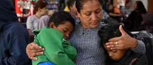 A mother seeking asylum holds her two sons.