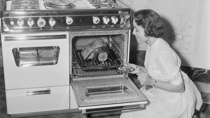 A black-and-white photo of a woman cooking a piece of meat in a gas oven