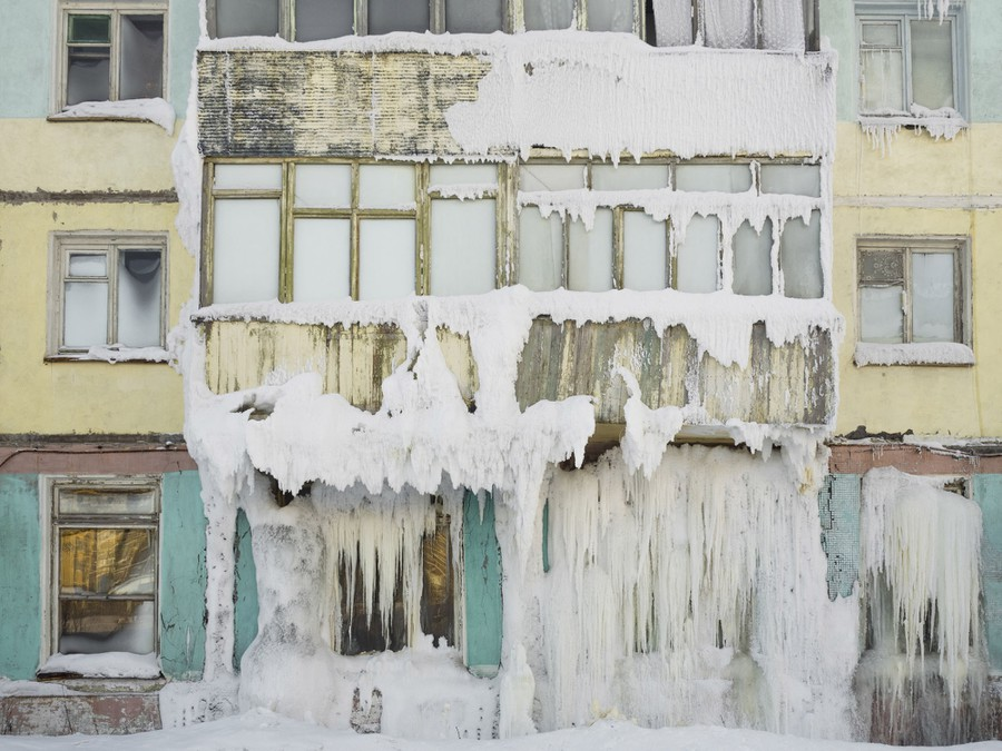 Large chunks of ice hang from the facade of an abandoned building.