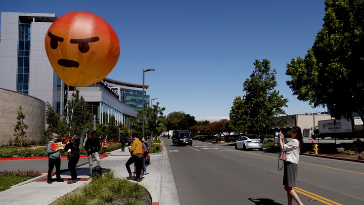 """People hold a balloon version of the """"angry"""" emoji."""