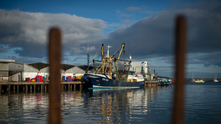 A fishing boat sits at a harbor on Britain's southern coast