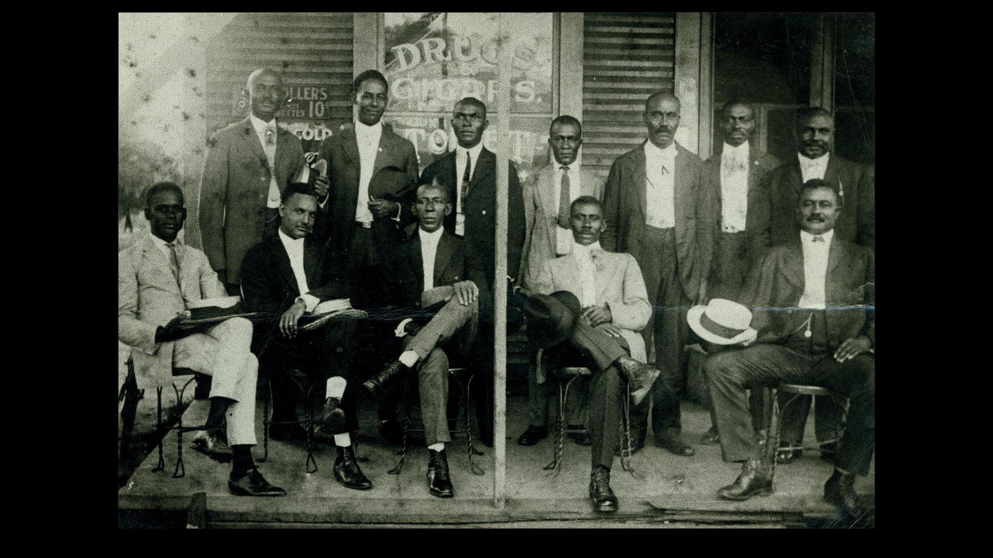 Men in suits sitting outside a drugstore