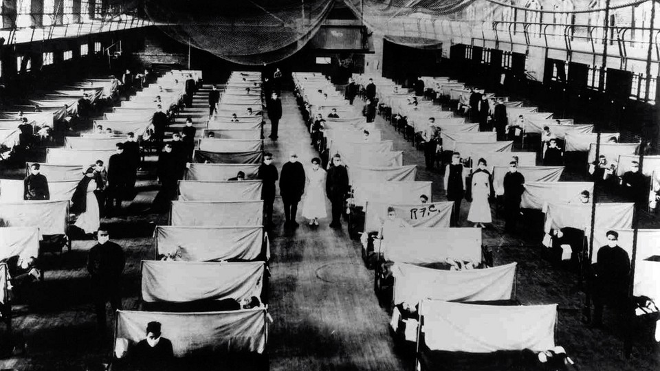 A historical photo of a flu hospital; rows of white-sheet partitions separate patients, and masked people stand in the corridors between them.