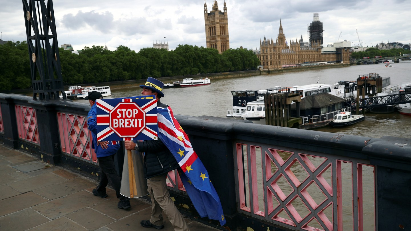 """An anti-Brexit campaigner crosses a bridge opposite Parliament in London holding a """"Stop Brexit"""" sign"""