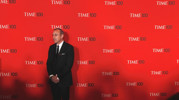 """Matt Lauer stands in a suit in front of a red backdrop with the words """"Time 100"""" written repeatedly behind him."""