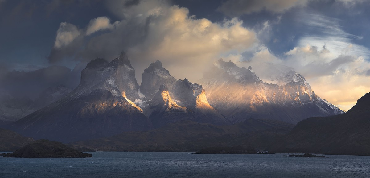 A view of distant mountains lit by a sunrise, among clouds