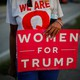 """A woman holding a """"Woman for Trump"""" sign."""