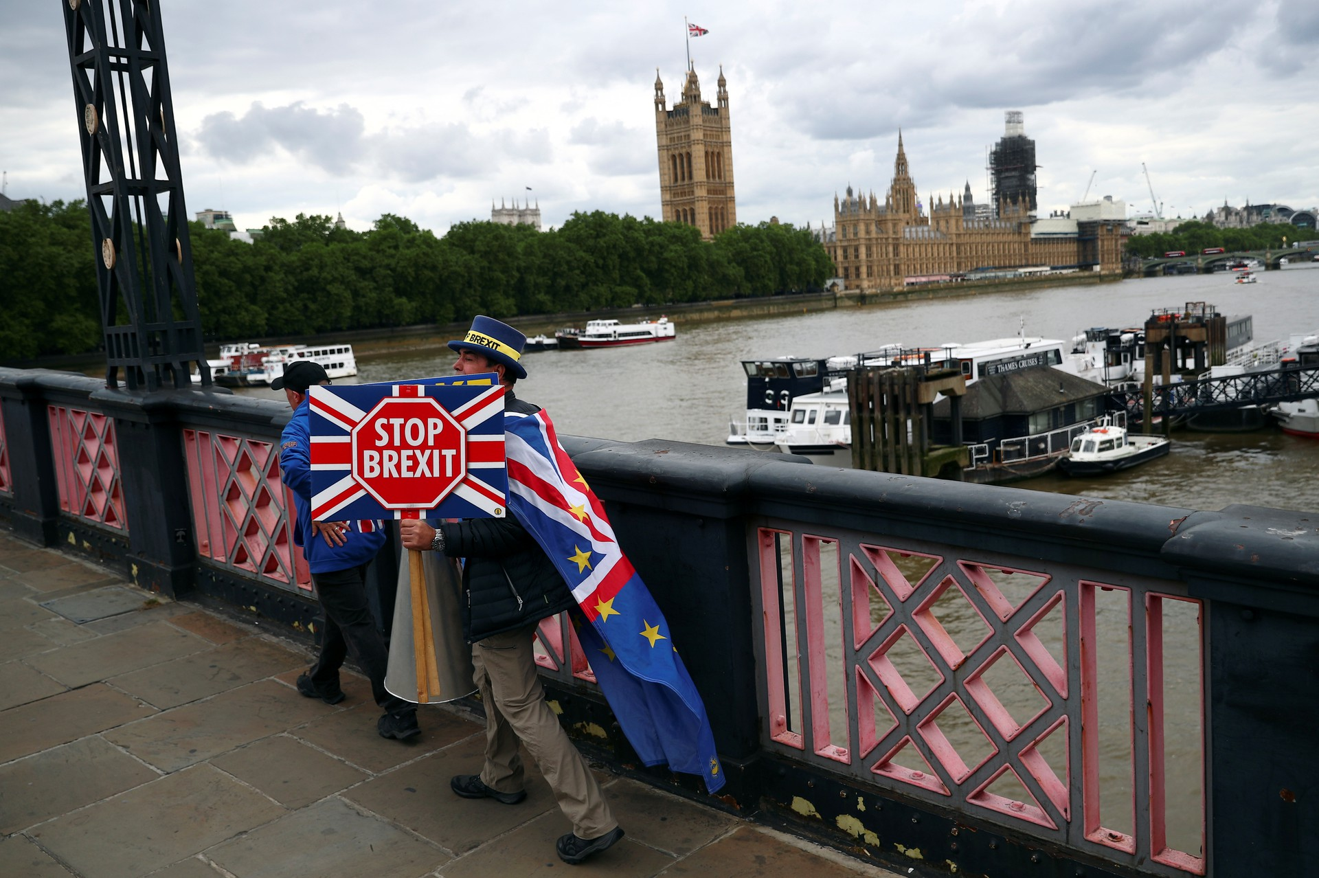 "An anti-Brexit campaigner crosses a bridge opposite Parliament in London holding a ""Stop Brexit"" sign"