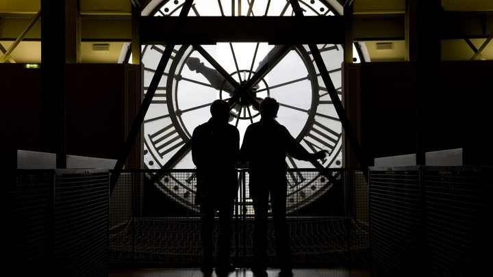 Two people are backlit while looking at a large clock