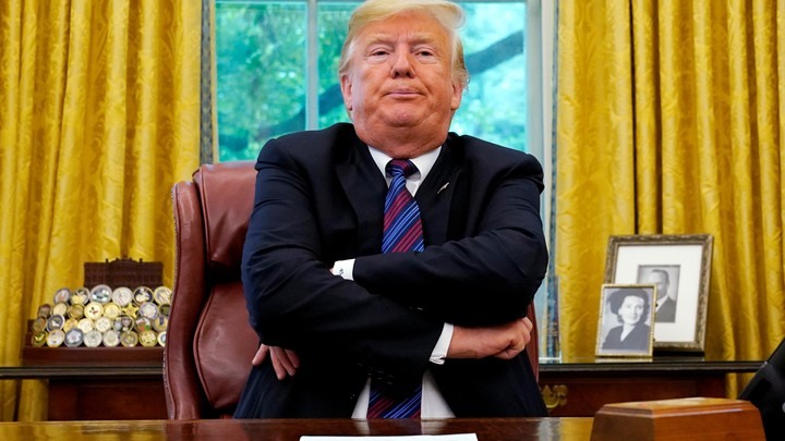 Trump sits at his desk with his arms crossed while announcing the new trade deal with Mexico.