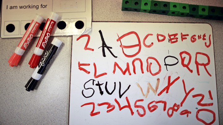 A whiteboard rests next to dry-erase markers and is covered in a student's attempts to scribble the alphabet.