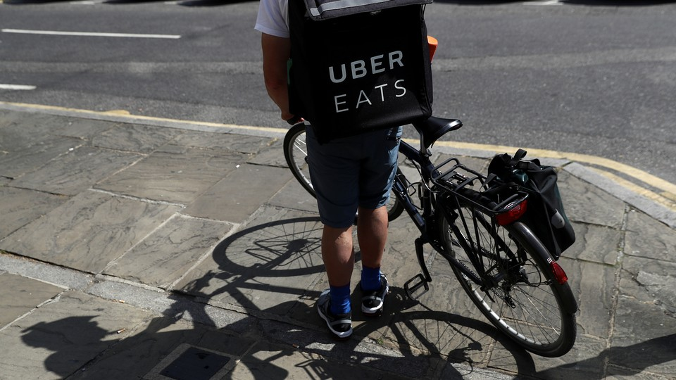 A cyclist prepares to delivery an Uber Eats food order.