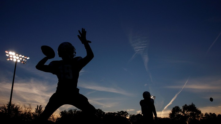 A silhouette of a high-school football player throwing a pass