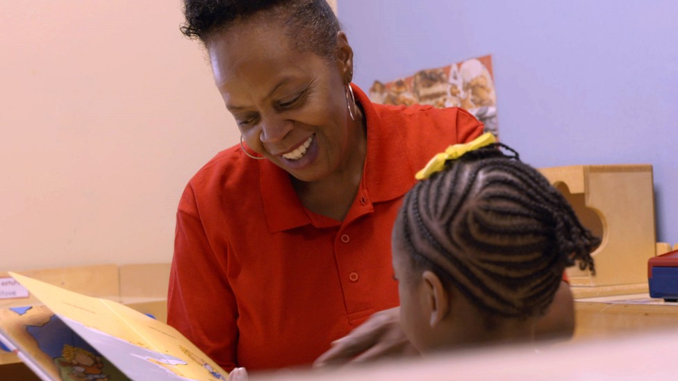 A woman reads to a child.