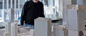 John Portman posing in front of architectural models inside his office.