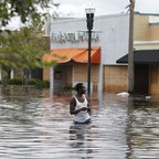 A man wades through a flooded street in front of boarded-up windows in Jacksonville, Florida