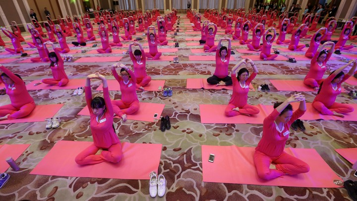 More than 1,000 pregnant women, all wearing pink, sit in a yoga class as part of an attempt to break an attendance record, in Beijing, in 2015.