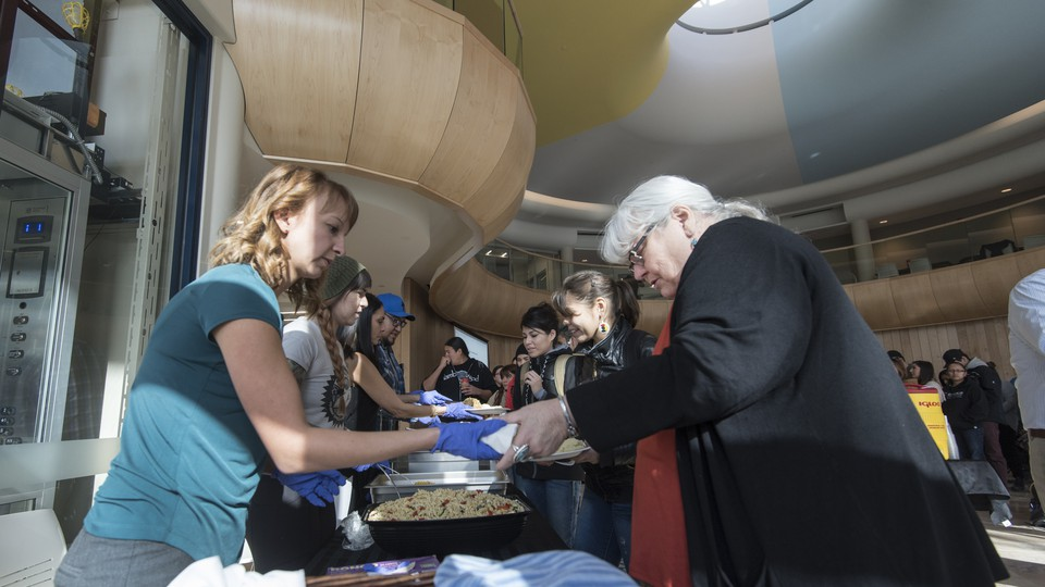 A woman is handed a plate of food. A line of other people is behind her.