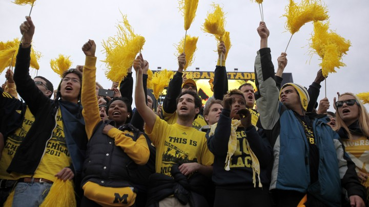 University of Michigan students hold yellow pom-poms and cheer in the stands of a football game.