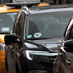 An Uber vehicle amidst taxis in New York City.