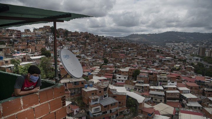 A person wearing a mask looks out over a view of the Petare slum in Caracas, Venezuela.