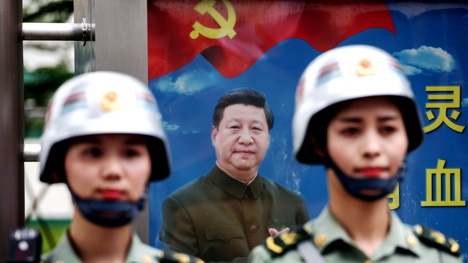Members of the People's Liberation Army stand in front of a poster featuring Chinese President Xi Jinping.