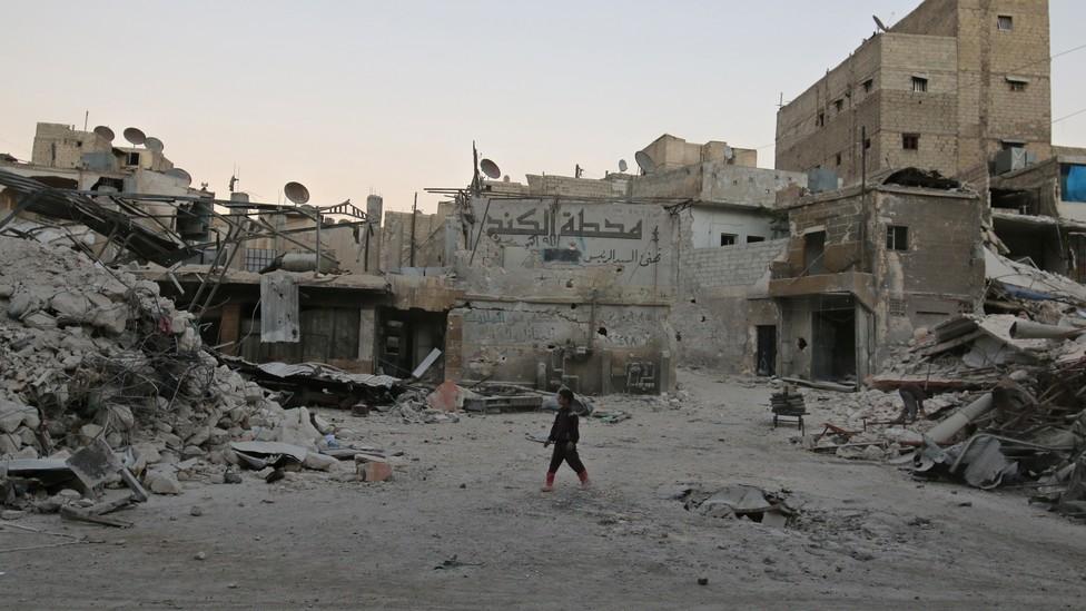 A boy walks amid damaged buildings in the rebel held area of al-Kalaseh neighbourhood of Aleppo.