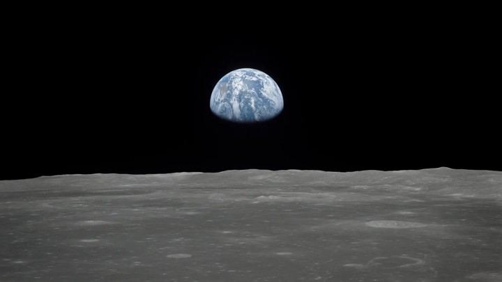 The Earth's sphere, partially occluded, hovers over the horizon of the moon.