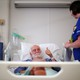 """A man giving the """"thumbs-up"""" sign in a British hospital bed"""