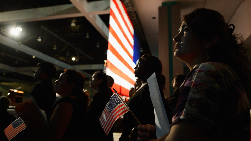 U.S.-citizenship candidates look at a video presentation as they wait to take the oath of citizenship at a naturalization ceremony.