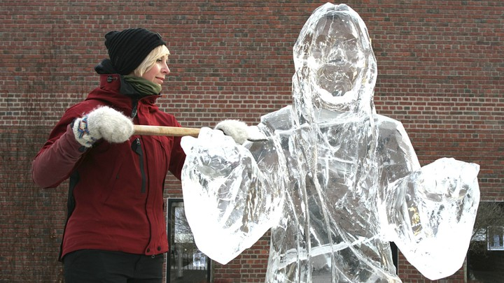 A woman raises an ice-scraping tool next to an ice sculpture of Jesus Christ.