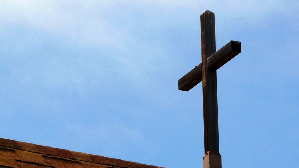 A wooden cross on a rooftop, against a blue sky