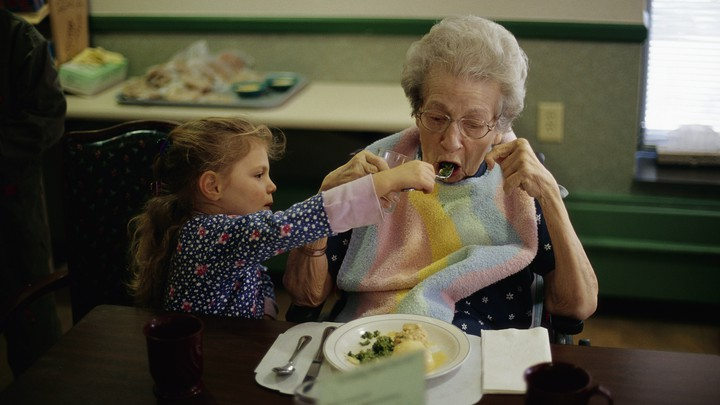 A toddler feeding an elderly woman from a fork.