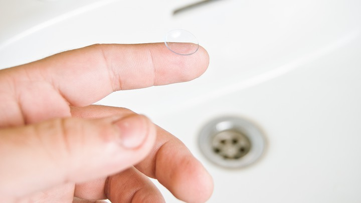 A finger holds a contact lense over a sink.