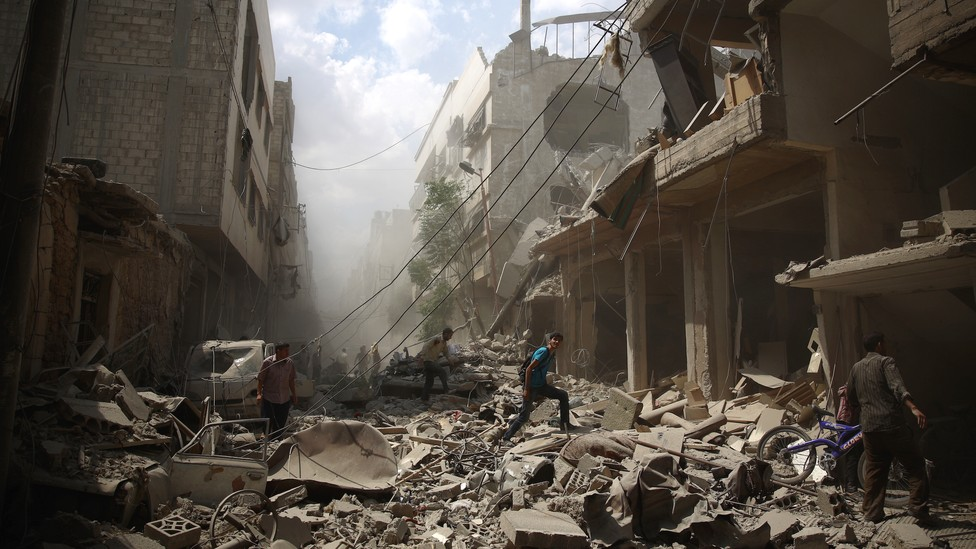 Syrians walk amid the rubble of destroyed buildings