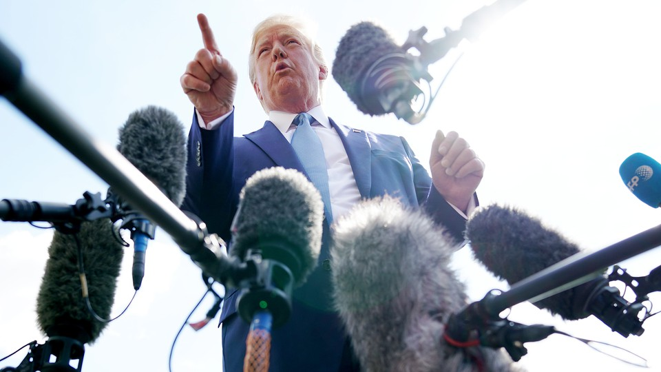 Donald Trump surrounded by microphones