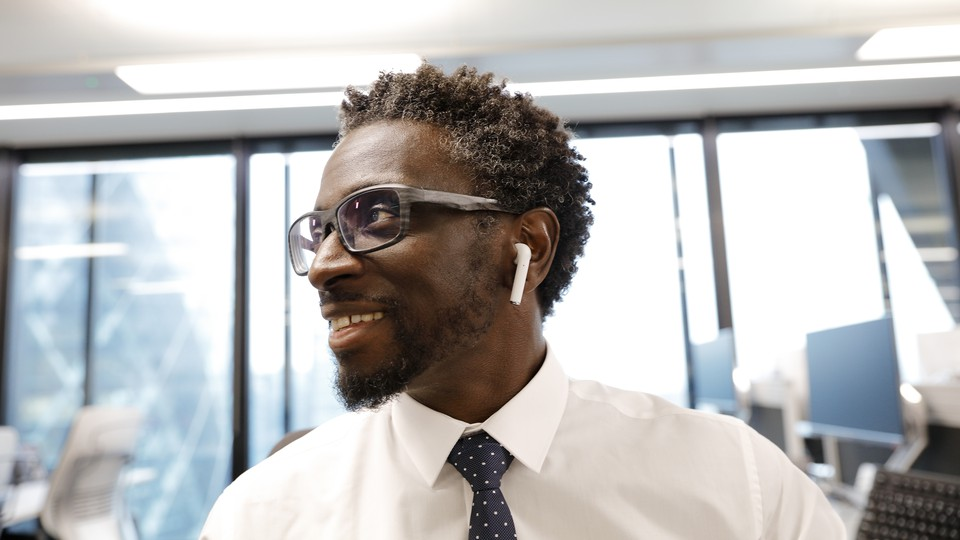 A man wearing Apple AirPod headphones smiles in an office