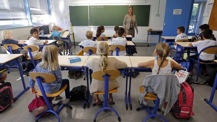 A teacher stands at the front of a classroom of students.