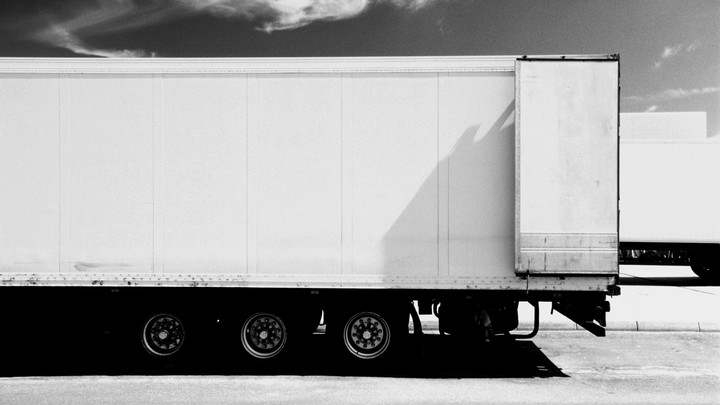 The trailer part of an 18-wheeler, painted white, dominates the frame